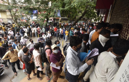 In this April 8, 2021 file photo, people wait in queues outside the office of the Chemists Association to demand necessary supply of the anti-viral drug Remdesivir, in Pune, India.