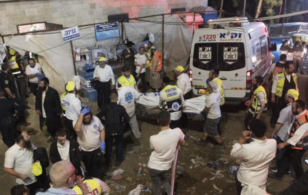 Israeli security officials and rescuers carry a body of a victim who died during a Lag Ba'Omer celebrations at Mt. Meron in northern Israel, Friday, April 30, 2021.