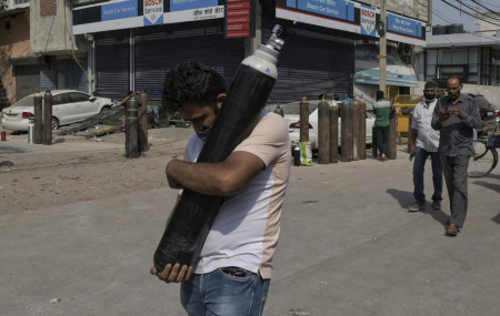 A man walks carrying a refilled cylinder as family members of COVID-19 patients wait in queue to refill their oxygen cylinders at Mayapuri area in New Delhi, India, Monday, May 3, 2021.