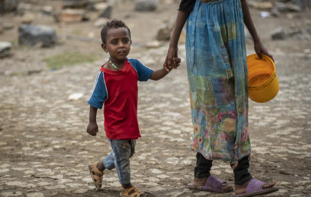 A displaced Tigrayan boy walks with a relative to receive food at the Hadnet General Secondary School which has become a makeshift home to thousands displaced by the conflict, in Mekele, in the Tigray region of northern Ethiopia Wednesday.