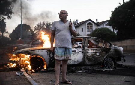 Jacob Simona stands by his burning car during clashes with Israeli Arabs and police in the Israeli mixed city of Lod, Israel Tuesday, May 11,2021.