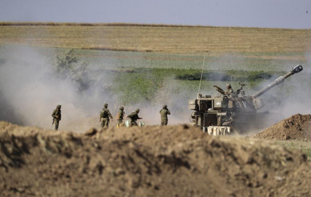 An Israeli artillery unit fires toward targets in Gaza Strip, at the Israeli Gaza border, Saturday, May 15, 2021.