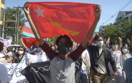 Anti-coup protesters display a party flag of the National League for Democracy (NLD) during a demonstration in Yangon, Myanmar, Friday, May 14, 2021.