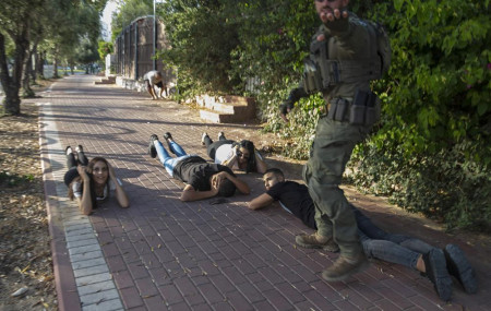 Israelis take cover as a siren sounds a warning of incoming rockets fired from the Gaza Strip, in Ashkelon, southern Israel, Sunday, May 16, 2021.