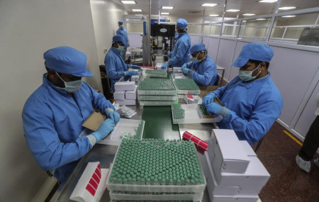 In this Jan. 21, 2021, file photo, employees pack boxes containing vials of Covishield, a version of the AstraZeneca vaccine at the Serum Institute of India in Pune, India.