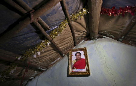 A portrait of Padmavathi, who died of COVID-19, hangs on the wall of her family hut made from bamboo and plastic sheeting in a slum in Bengaluru, India, Thursday, May 20, 2021.