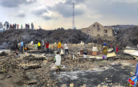 People gather on a stream of cold lava rock following the overnight eruption of Mount Nyiragongo in Goma, Congo, Sunday, May 23, 2021.