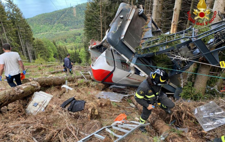 Rescuers work by the wreckage of a cable car after it collapsed near the summit of the Stresa-Mottarone line in the Piedmont region, northern Italy, Sunday, May 23, 2021.