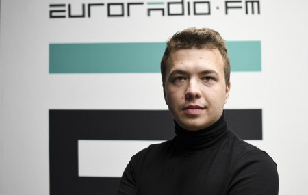 In this handout photo released by European Radio for Belarus, Belarus journalist Raman Pratasevich poses for a photo in front of euroradio.fm sign in Minsk, Belarus, Sunday, Nov. 17, 2019.