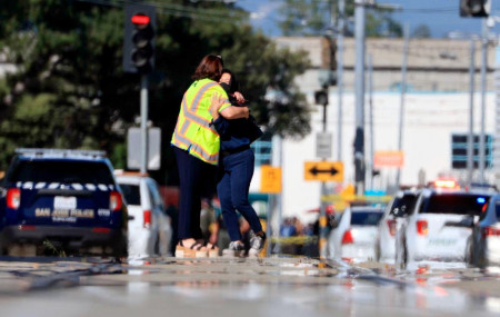 Two people hug on Younger Avenue outside the scene of a shooting in San Jose, Calif., on Wednesday, May, 26. 2021.