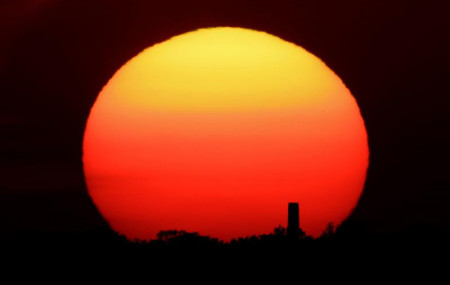 In this Friday, June 26, 2020 file photo, the sun sets behind a smokestack in the distance in Kansas City, Missouri.