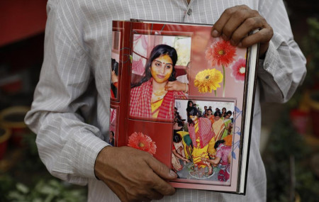 Radha Gobindo Pramanik holds photographs of his daughter who died of COVID-19 in Lucknow, India, Thursday, June 3, 2021.