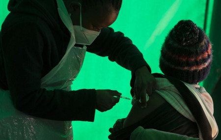 In this Thursday, June 3, 2021, file photo, an elderly patient receives a dose of the Pfizer COVID-19 vaccine at a clinic at Orange Farm, near Johannesburg.