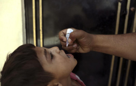 A health worker administers a vaccination to a child during a polio campaign in the old part of Kabul, Afghanistan, Tuesday, June 15, 2021.