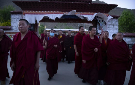 Monks prepare to go to dinner at the Tibetan Buddhist College near Lhasa in western China's Tibet Autonomous Region, Monday, May 31, 2021, as seen during a government organized visit for foreign journalists.
