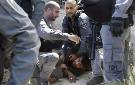 Israeli police officers detain a Palestinian man during clashes that erupted ahead of a planned march by Jewish ultranationalists through east Jerusalem, outside Jerusalem's Old City, Tuesday, June 15, 2021.