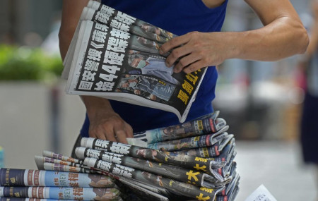 In this Friday, June 18, 2021, file photo, a vendor adjusts copies of Apple Daily newspapers at a newsstand in downtown Hong Kong.