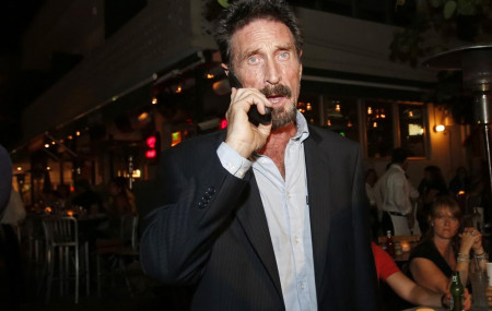 In this Dec 12, 2012 file photo, anti-virus software founder John McAfee talks on his mobile phone as he walks on Ocean Drive in the South Beach area of Miami Beach, Florida.