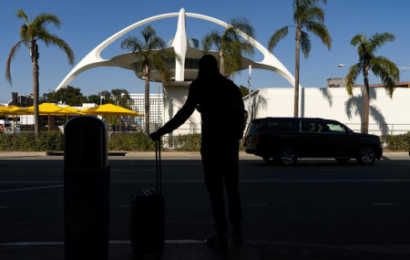 In this Nov. 25, 2020, file photo, a traveler awaits for transportation at the Los Angeles International Airport in Los Angeles.