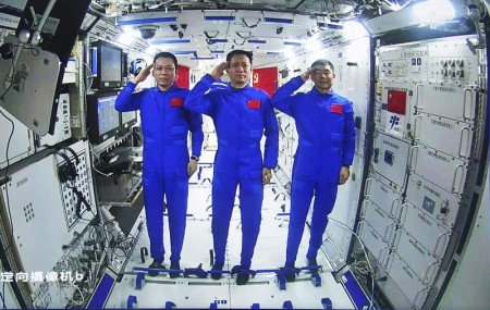 Chinese astronauts, from left; Tang Hongbo, Nie Haisheng, and Liu Boming salute from aboard China's space station core module Tianhe during a video conversation with Chinese President Xi Jinping, Wednesday.