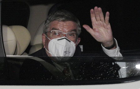 International Olympic Committee (IOC) President Thomas Bach waves from the vehicle to media upon his arrival an accommodation Thursday, July 8, 2021, in Tokyo.