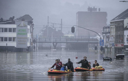 People use rubber rafts in floodwaters after the Meuse River broke its banks during heavy flooding in Liege, Belgium, Thursday, July 15, 2021.