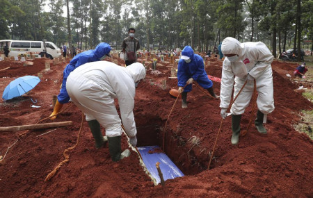 In this July 14, 2021, photo, workers in protective gear lower a coffin of a COVID-19 victim to a grave for burial at the Cipenjo Cemetery in Bogor, West Java, Indonesia.