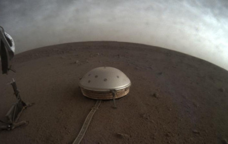 In this undated photo made available by NASA on Thursday, July 22, 2021, clouds drift over the dome-covered SEIS seismometer of the InSight lander on the surface of Mars.