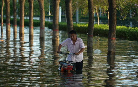 In this July 26, 2021, file photo, a man pushes a scooter through floodwaters in Xinxiang in central China's Henan Province, Monday, July 26, 2021.