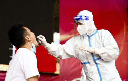 In this July 5, 2021, file photo released by Xinhua News Agency, a medical worker collects a swab sample for nucleic acid test in Ruili City of southwest China's Yunnan Province.