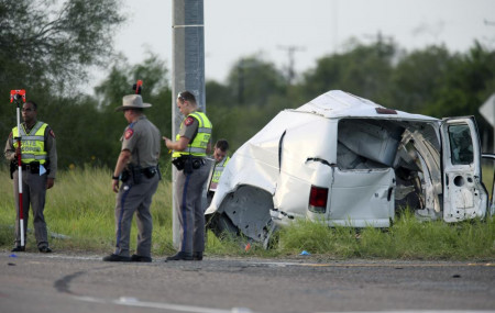 Texas Department of Public Safety officers stand near a vehicle where multiple people died after the van carrying migrants tipped over just south of the Brooks County community of Encino on Wednesday, Aug. 4, 2021, in Encino, Texas.