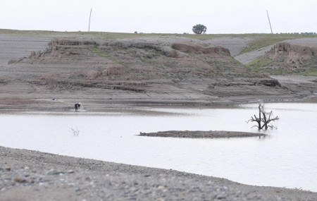 In this photo taken from a video shot on Wednesday, Aug. 4, 2021 in Wad el-Hilu, Sudan, a man washes in the Setit river, known in Ethiopia as Tekeze River.