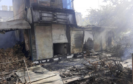 Smoke rises from damaged shops after fighting between Taliban and Afghan security forces in Kunduz city, northern Afghanistan, Sunday, Aug. 8, 2021.