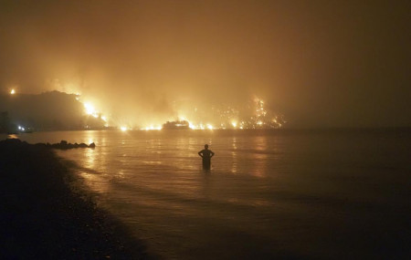 In this file photo dated Friday, Aug. 6, 2021, a man watches as wildfires approach Kochyli beach near Limni village on the island of Evia, about 160 kilometers (100 miles) north of Athens, Greece.