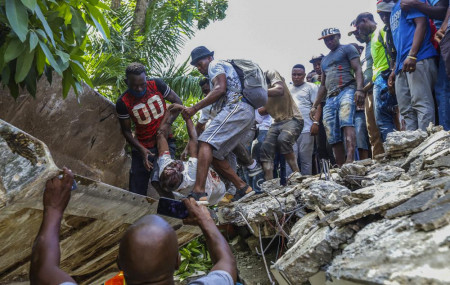 People recover the body of Jean Gabriel Fortune, a longtime lawmaker and former mayor of Les Cayes, from the rubble of the Hotel Le Manguier destroyed by the earthquake in Les Cayes, Haiti, Saturday, Aug. 14, 2021.