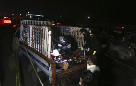 Pakistani investigators examine a truck at the site of an explosion, in Karachi, Pakistan, Saturday, Aug. 14, 2021.