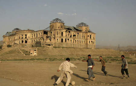 In this July 1, 2008 file photo, Afghans play football in front of the destroyed Darul Aman Palace in the western part of Kabul, Afghanistan.