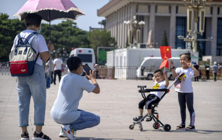 Children hold Chinese flags as they pose for a photo at Tiananmen Square in Beijing, on June 22, 2021.