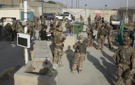 In this photo provided by the Ministry of Defence, members of the British and US military engage in the evacuation of people out of Kabul, Afghanistan on Friday, Aug. 20, 2021.