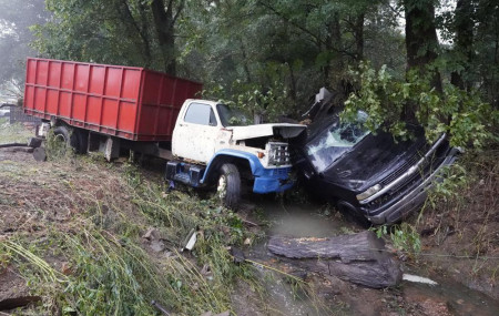A truck and a car sit in a creek Sunday, Aug. 22, 2021, after they were washed away the day before in McEwen, Tennessee.