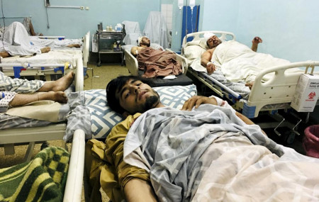 Wounded Afghans lie on a bed at a hospital after a deadly explosions outside the airport in Kabul, Afghanistan, Thursday, Aug. 26, 2021.