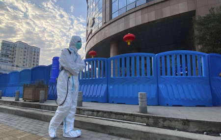 In this Feb. 6, 2021, file a worker in protectively overalls and carrying disinfecting equipment walks outside the Wuhan Central Hospital in China.