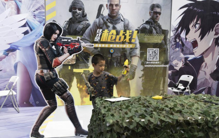 A child plays with a toy gun during a promotion for online games in Beijing on Saturday, Aug. 29, 2020.