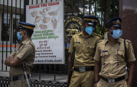 Police personnel wearing masks guard outside the Reserve Bank of India during a protest against the federal government's plan to privatize government assets in Kochi, Kerala state, India, Tuesday, Aug.31, 2021.