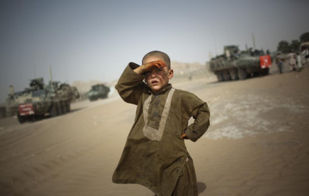 In this Aug. 6, 2009 file photo, a child watches military vehicles of 5th Striker Brigades drive past his village on the outskirts of Spin Boldak, about 100 kilometers (63 miles) southeast of Kandahar, Afghanistan.