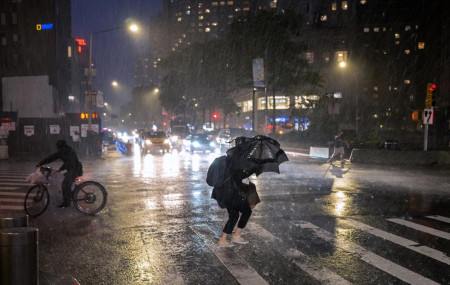Pedestrians take cover near Columbus Circle in New York Wednesday, Sept. 1, 2021, as the remnants of Hurricane Ida remained powerful while moving along the Eastern seaboard.