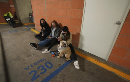 People gather outside thier building with their pet after a strong earthquake, in Mexico City, Tuesday, Sept. 7, 2021.