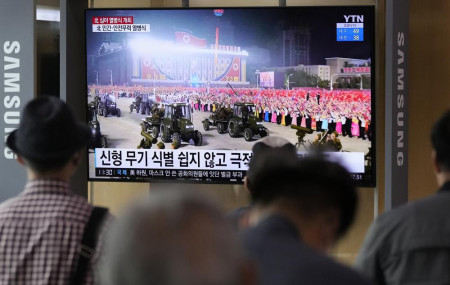 People watch a TV showing a military parade held in Pyongyang, North Korea, at Seoul Railway Station in Seoul, South Korea, Thursday, Sept. 9, 2021.