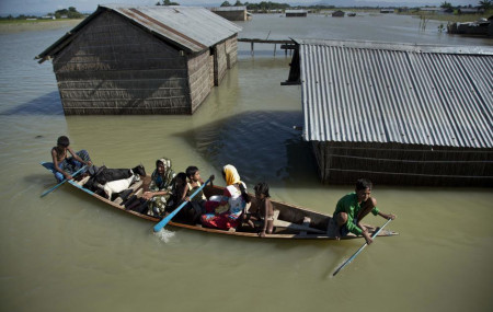 In this July 31, 2016, file photo, a flood-affected family with their goats travel on a boat in the Morigaon district, east of Gauhati, northeastern Assam state, India.