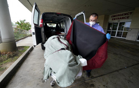 In this Aug. 18, 2021, file photo, an employee of a local funeral home covers the body of a COVID-19 patient who died as he prepares to take it away from a loading dock, at the Willis-Knighton Medical Center in Shreveport, Louisiana.